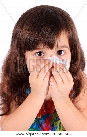 Niña limpiando la nariz con pañuelo