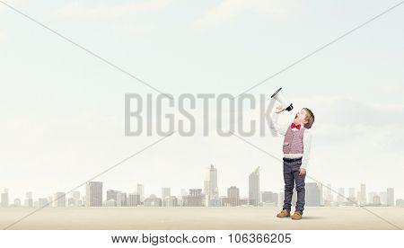 Little sweet boy screaming emotionally into megaphone