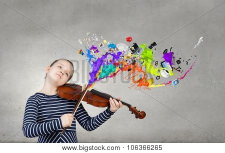 Cute kid girl playing violin and colorful splashes flying out