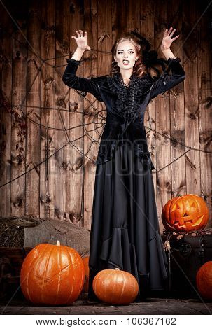 Portrait of a beautiful witch lady in black dress standing with pumpkins over wooden background. Halloween.