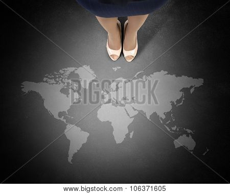 Top view of businesswoman feet and world map on floor
