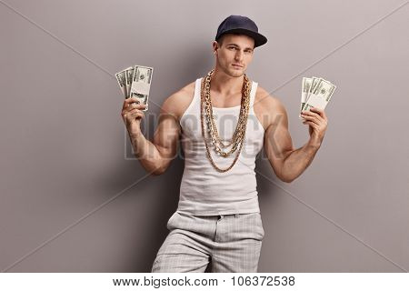 Young male rapper with golden chain around his neck holding few stacks of money and looking at the camera