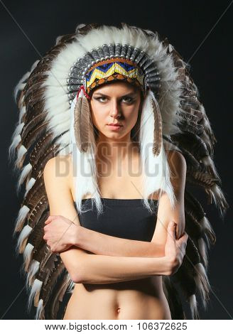 Beautiful woman in native american costume with feathers