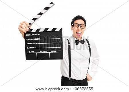 Excited young movie director holding a clapperboard and looking at the camera isolated on white background