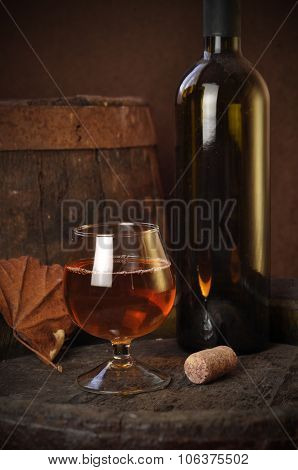 Glass Of Brandy In The Cellar With Old Barrels Stacked