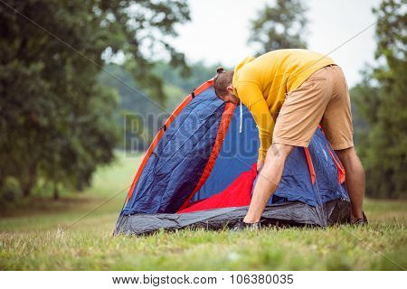 Handsome hipster pitching his tent in the countryside