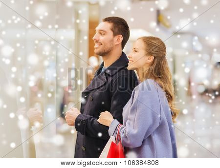 sale, consumerism and people concept - happy young couple with shopping bags looking to shopwindow in mall with snow effect