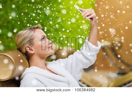 people, beauty, lifestyle, technology and relaxation concept - beautiful young woman in white bath robe taking selfie with smartphone at spa with snow effect