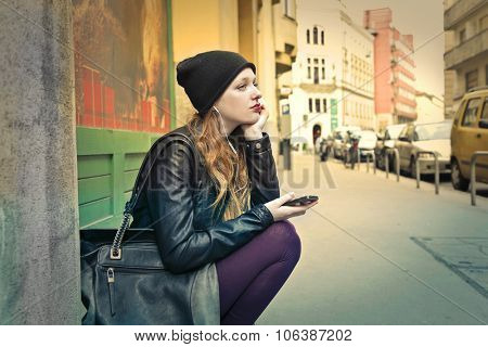 Bored girl sitting on the ground listening to music