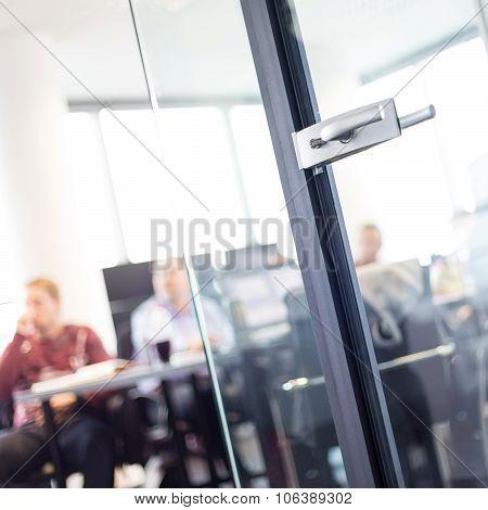 Trough glass door view of corporate meeting.
