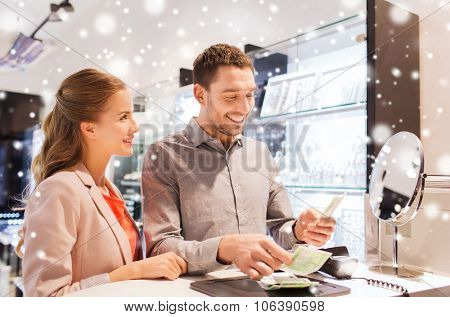 sale, consumerism, shopping and people concept - happy couple with money paying for purchase in jewelry store with snow effect