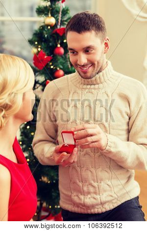 love, couple, christmas, x-mas, winter, relationship and dating concept - romantic man proposing to a woman in red dress
