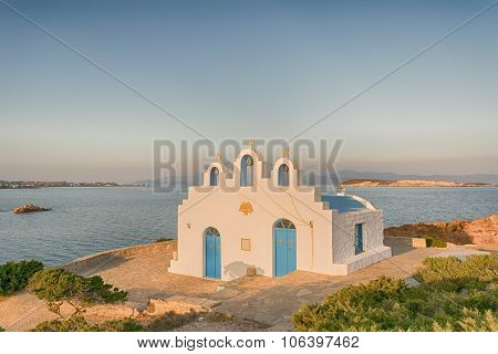 Local church in Pirgaki in Paros island against the blue Aegean sea. A beautiful landscape.