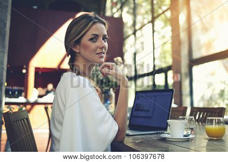 Young pretty female using net-book while sitting in modern cafe interior
