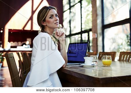 Charming blonde female sitting at the table with open net-book during morning breakfast