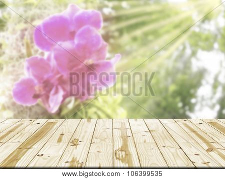 Wood table top on orchid flowers with sunrays blurred