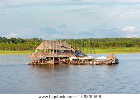 IQUITOS, PERU - OCTOBER 16, 2015: Al Frio y Al Fuego Restaurant. The floating restaurant on the Itaya River offers fine service and excellent Peruvian fusion cuisine and a floating pool.