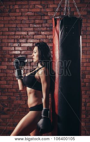 Young sexy girl with boxing gloves, punching bag,on the background wall of red brick.