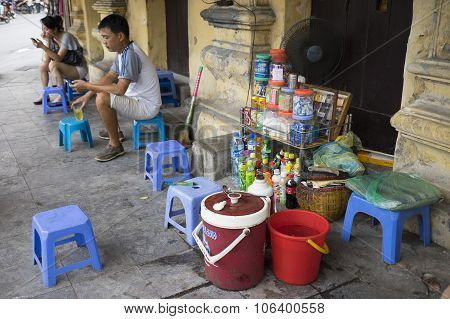 A flea mobile beverage stall on the sidewalk of a street in Hanoi