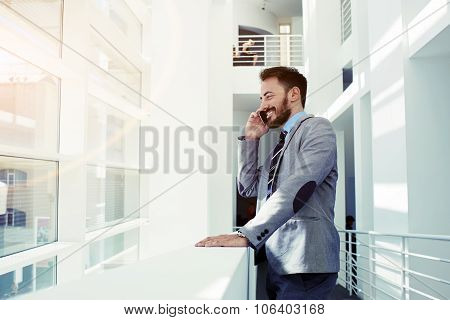 Cheerful smiling men office worker talking on mobile phone while standing in modern office space