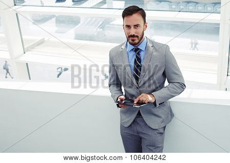 Confident male boos dressed in corporate clothing using digital tablet during work break