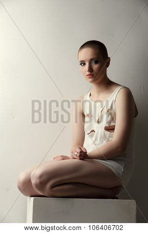 Cute skinhead girl in torn T-shirt posing as crazy