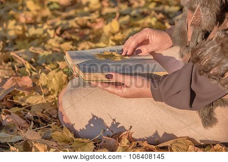 Woman  holding a book on the autumn leaves
