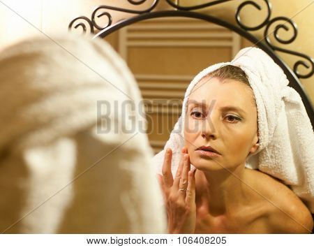 Middle-aged woman checking her face in bathroom mirror after shower