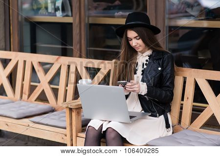 Female freelancer chatting on cell telephone while sitting with net-book outdoors