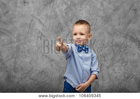 Portrait Of A Cute Little Boy In Jeans, Blue Shirt And Bow Tie On A Gray Textural Background In Stud