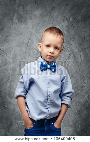 Portrait Of A Cute Little Boy In Jeans, Blue Shirt And Bow Tie