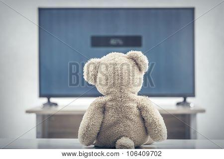 Teddy bear watching television.