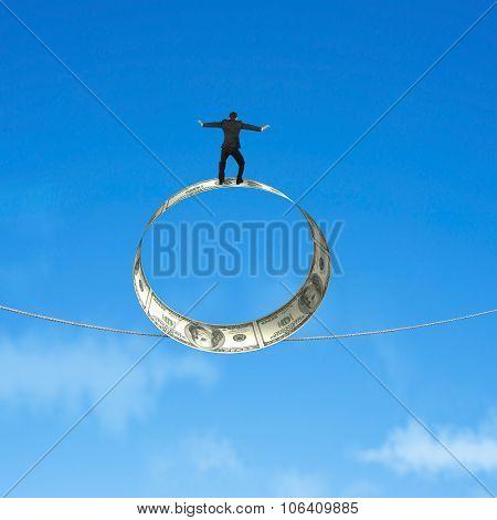 Man Standing On Roll Of Dollar Bills Balancing Tightrope