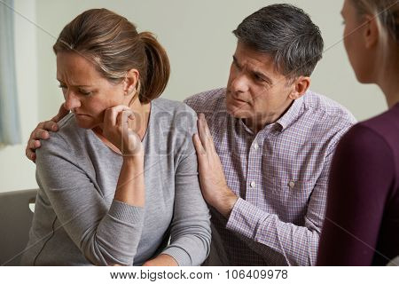 Mature Couple Talking With Counsellor As Man Comforts Woman
