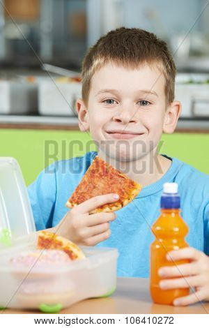 Male Pupil Sitting At Table In School Cafeteria Eating Unhealthy Packed Lunch