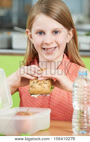 Female Pupil Sitting At Table In School Cafeteria Eating Healthy Packed Lunch