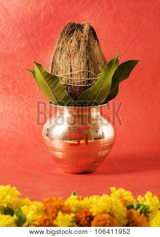 copper kalash with coconut and mango leaf with floral decoration. essential in hindu puja, front vie