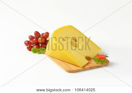 wedge of fresh cheese with red grapes on wooden cutting board