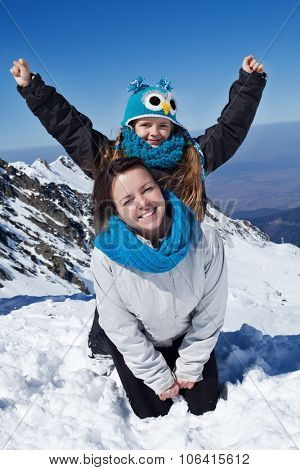 Enjoying the first snow in the mountains - woman and little girl on a cliff