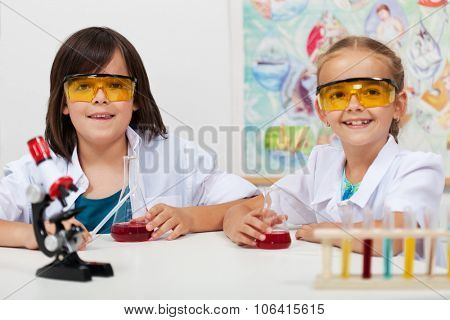 Kids in elementary science class doing chemical experiments-focus on boy face