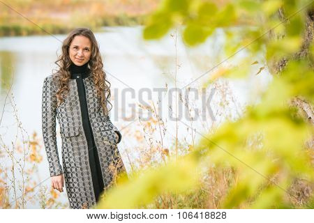 Portrait Of A Young Girl On The Background Of Autumn River With Blurred Leaves In The Foreground