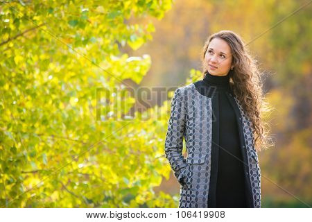 Cute Young Girl Looking To The Left On The Background Of Autumn Yellow Foliage