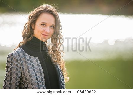 Portrait Of A Young Girl On A Background Autumn Coat River