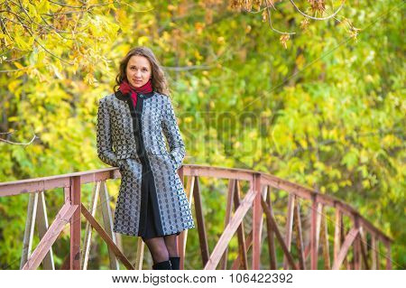 Cute Young Girl Leaned On The Railing Of The Bridge Against The Backdrop Of Autumn Leaves Yellow