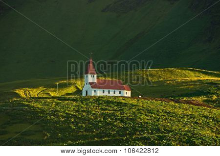 Wooden church on top of green hill at sunrise, Vik, Iceland