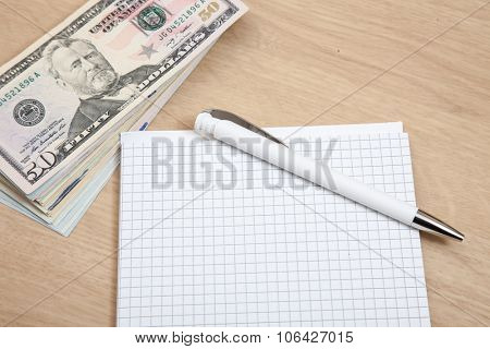 Various dollar notes next to notepad