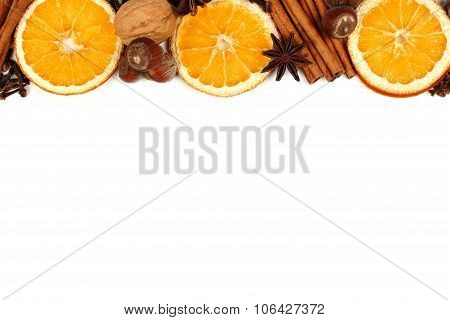 Border of holiday spices and baking ingredients over white