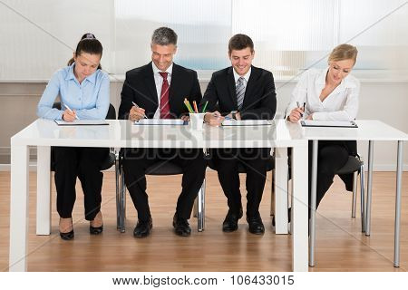 Businesspeople Writing On Clipboard
