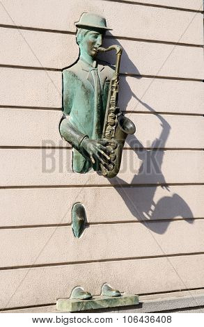 Bronze statue of saxophonist coming through the wall on Rustaveli street in old Tbilisi Georgia
