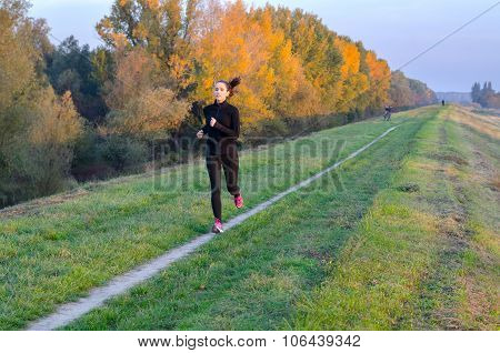 Beautiful Slim Girl Running In Nature On Sunny Autumn Day